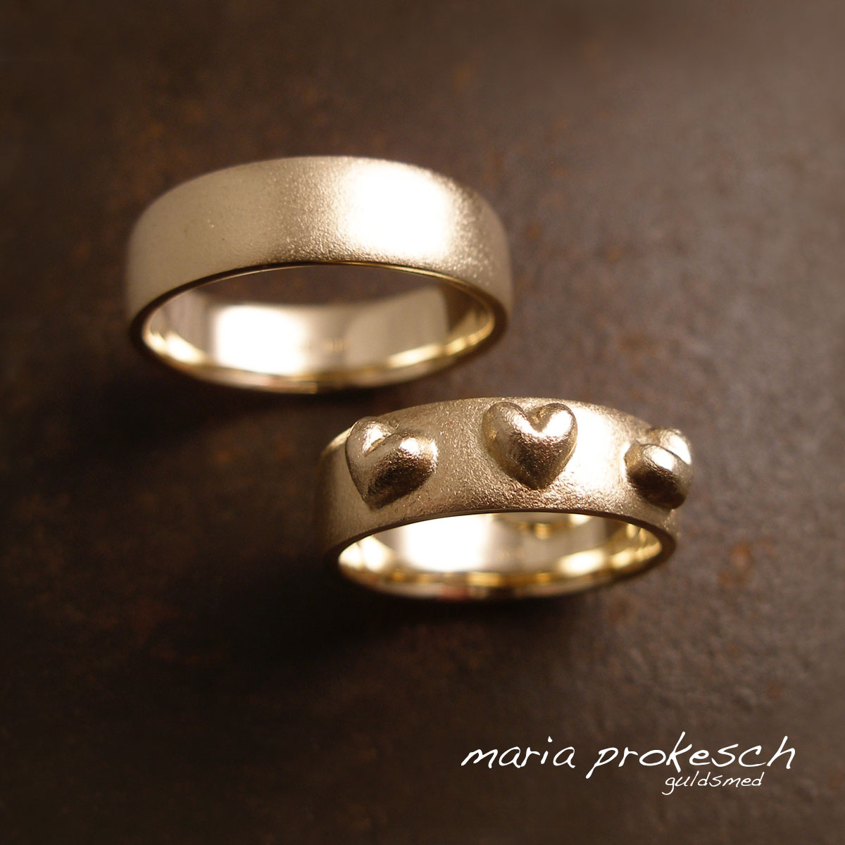 Rustikke forlovelsesringe med tre ophøjede buttede hjerter. Et utraditionel anderledes design. Håndlavet fra eget værksted efter jeres valg.