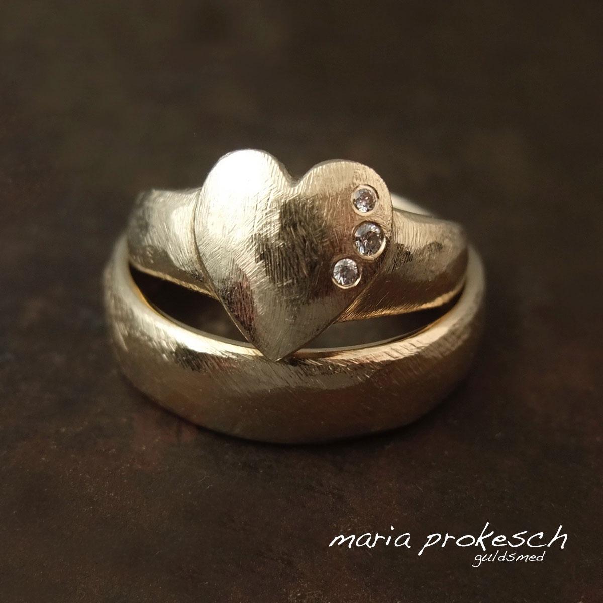 Kærlighedsringe med hjerte i kvindens ring. Vielsesringene er rustikke med groft filet overflade og sten, tre diamanter i hendes hjerte