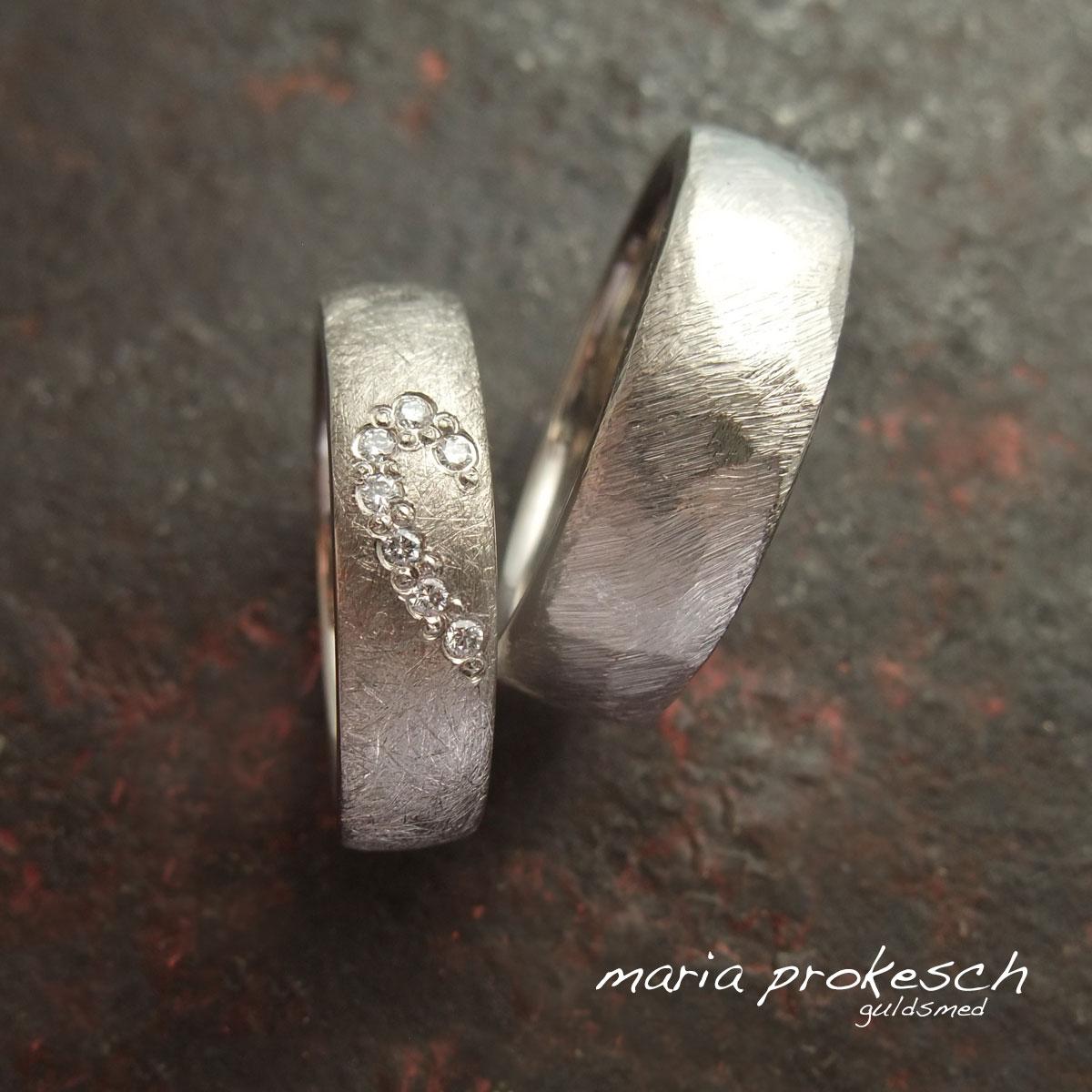 Kærlighedsringe med sten, hvide diamanter, der sidder i et halvt hjerte i kvindens ring. Begge ringe er i hvidguld med hver deres individuelle rustikke overflade