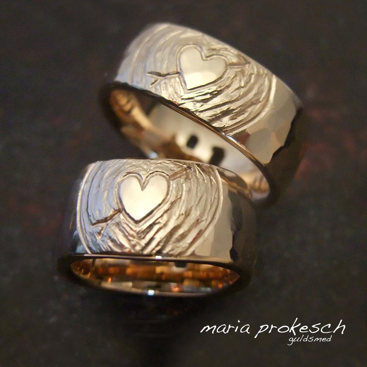 Vielsesringe i 14 kt rødguld, begge med hjerter med personlig amor pil i to rustikke overflader. Kærlighedshistorie som evigt minde i ringene.