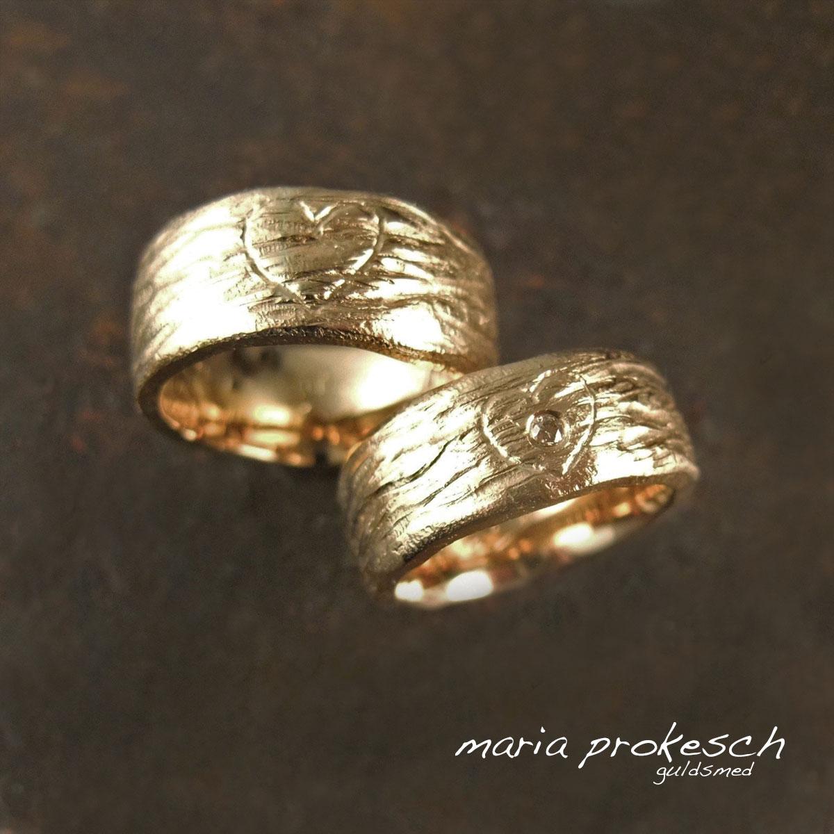 Vielsesringe i 14 kt gult guld med grov barkoverflade og buttet hjerte ridset som evigt minde. Hendes med en gylden diamant.