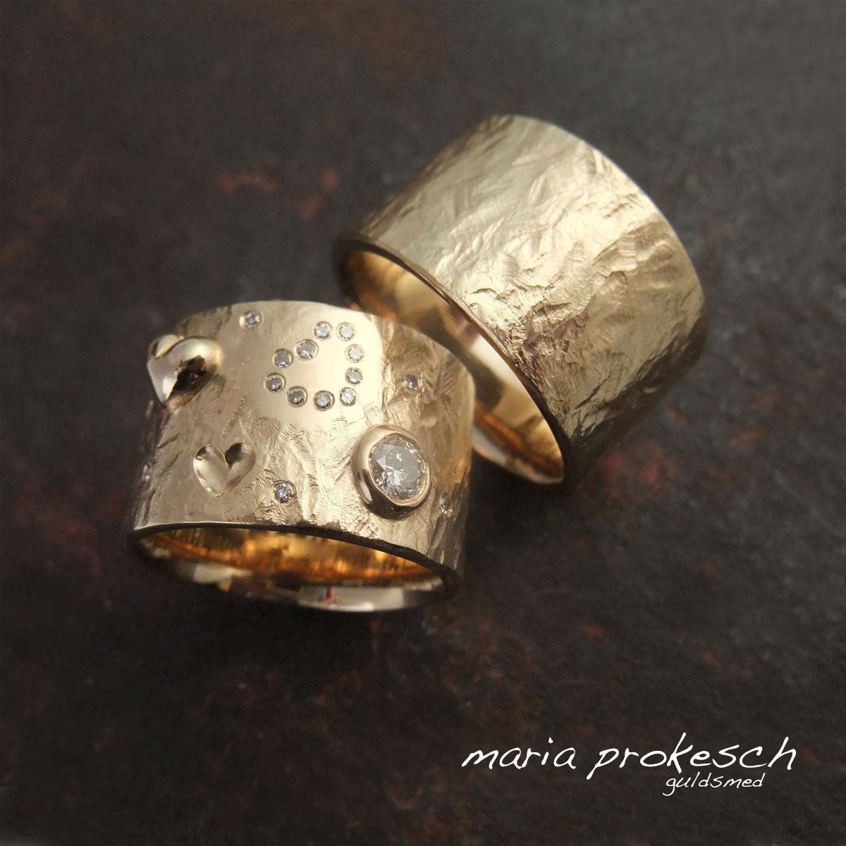 Bredde vielsesringe i 14 kt guld begge med rustikke overflader. Hendes med hjerter, som fordybning, som ophøjet og med små brillanter placeret som hjerte. En stor diamant i rørfatning og små diamanter strøet giver endnu mere blikfang.
