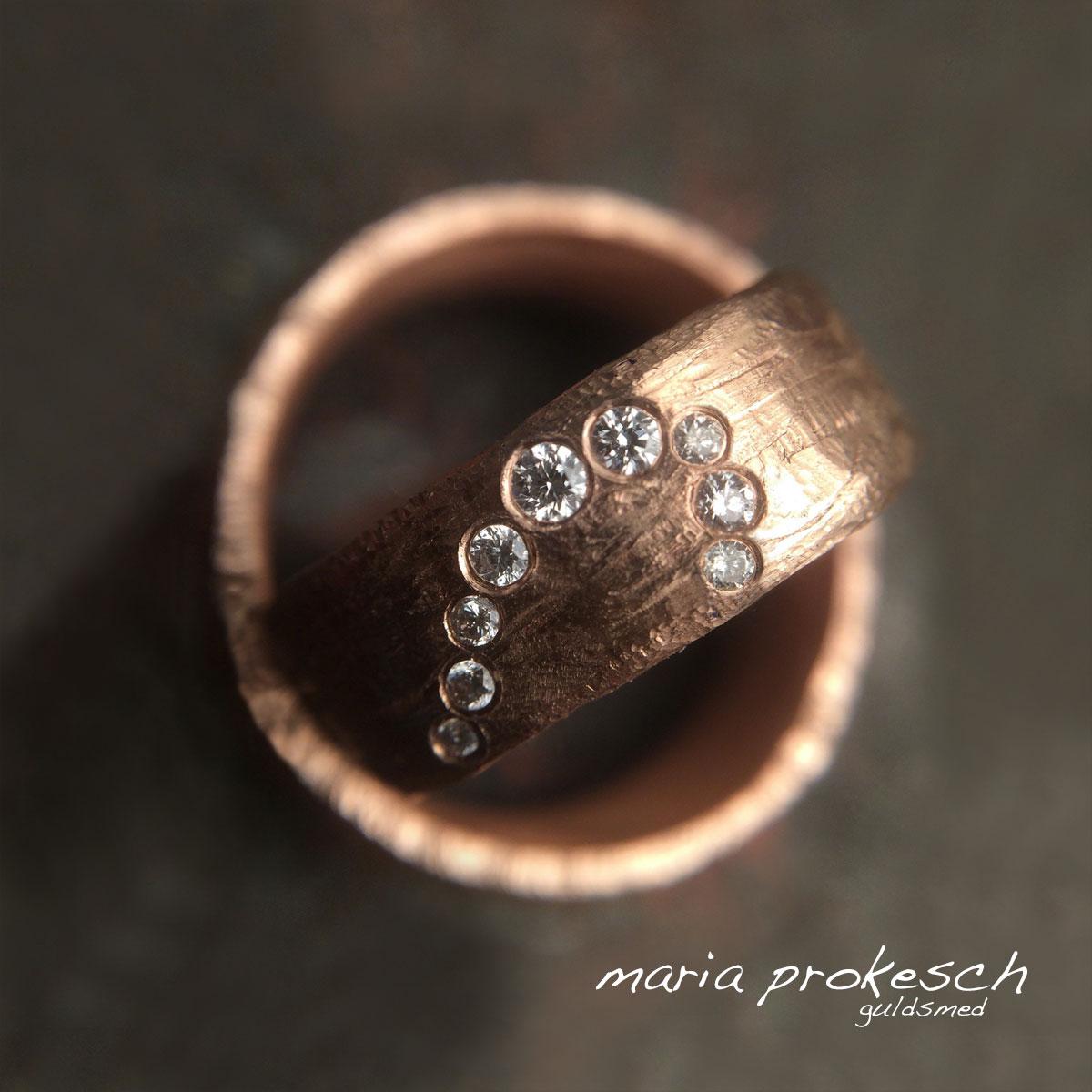 Vielsesringe i 14 kt rosaguld, hvor halve hjerte forbinder dem. På hendes ring er det brillanter i forskellige størrelse som danner det halve hjerte. På hans ring er det en gravering. Begge ringe har en rustik overflade.