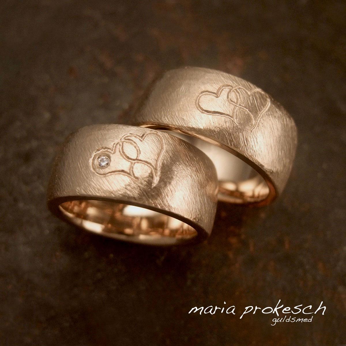 Vielsesringe i 14 kt guld med dobbelte hjerter, efter personlig tegning og ønsker. Begge guldringe er håndlavede bredde ringe og har filet grov overflade.