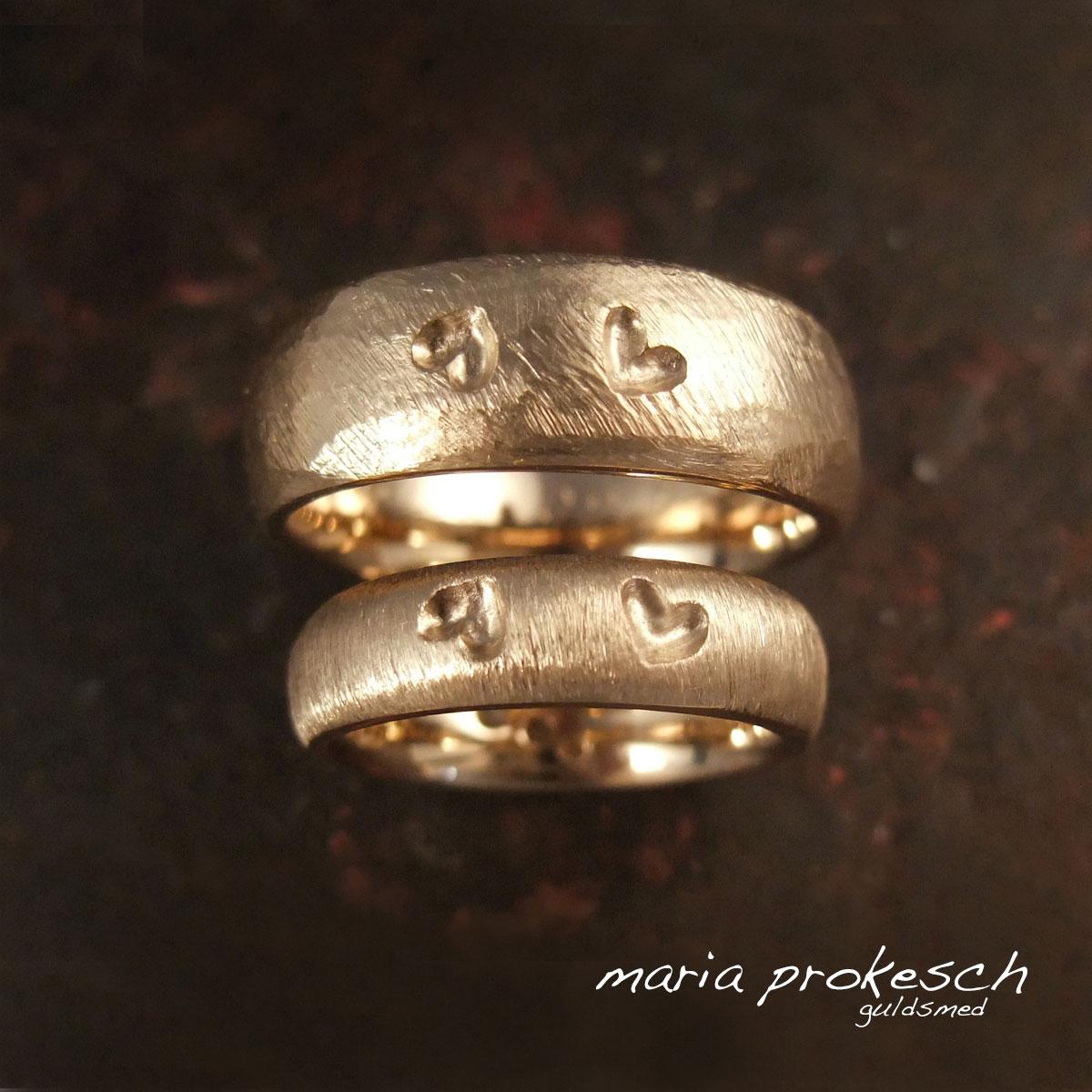 Hjerte vielsesringe i 14 kt guld, rustikke overflader med to hjerter som fordybninger. Håndlavet efter kundernes personlige ønsker
