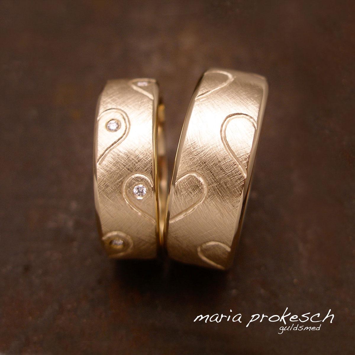 Vielseringe i 14 kt guld, begge ringe med graverede halve hjerter som symbolisere parrets børn og fælles kærlighed