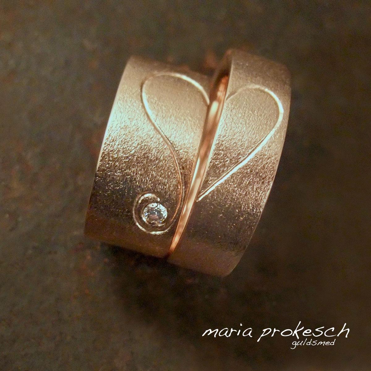 Vielsesringe med personlige halve hjerte i 14 kt rosaguld. Ringene er matteret i overfladen. Hendes med brillant i en elegant krølle fra hendes hjerte.