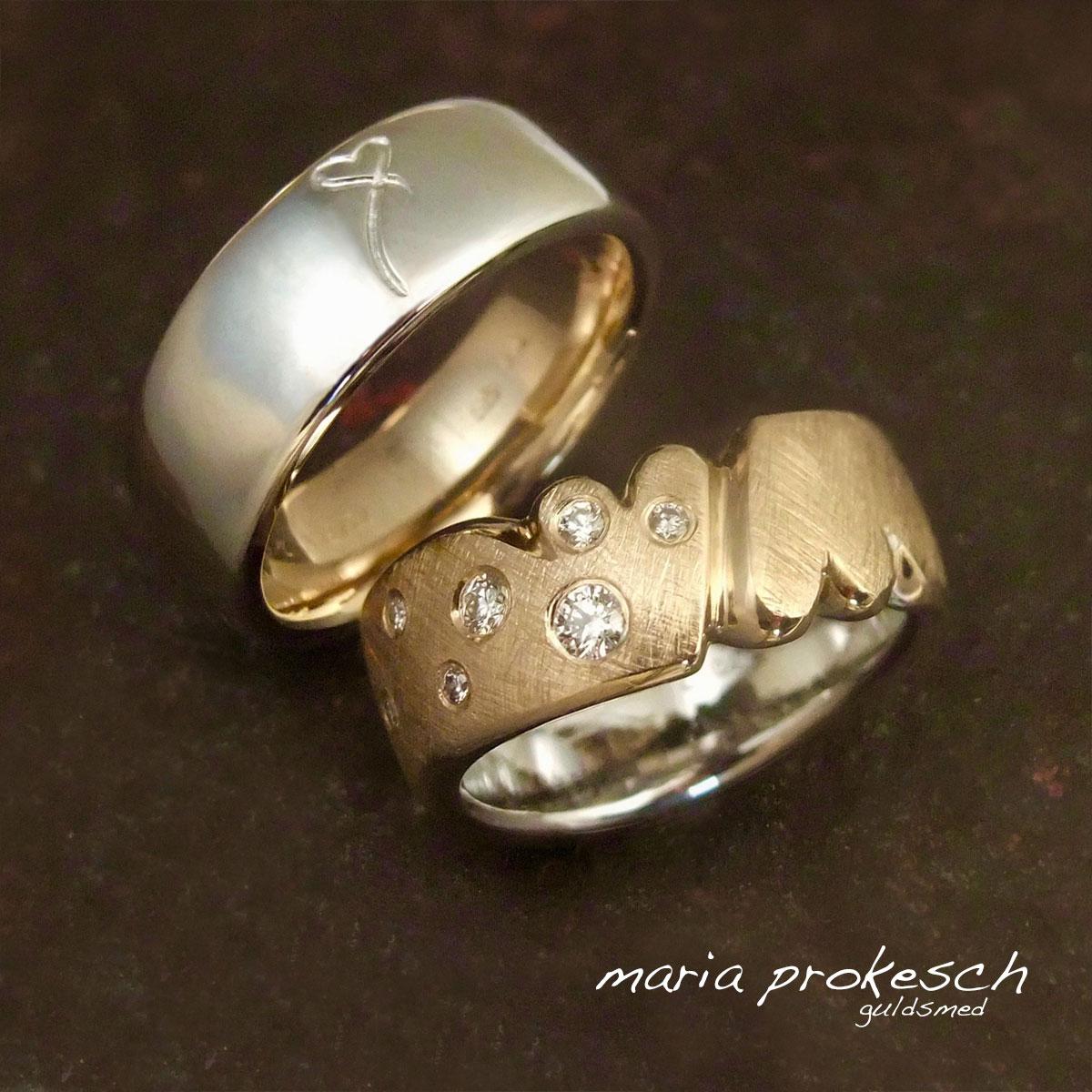 Personlige vielsesringe med samhørighed og hjerter. Hendes ring med rødguld yderst og hvidguld inderst, hans omvendt. I hendes ring er der to hjerter filet utraditionelt, og med brillanter. På hans ring et hjerte som hun har tegnet til ham.