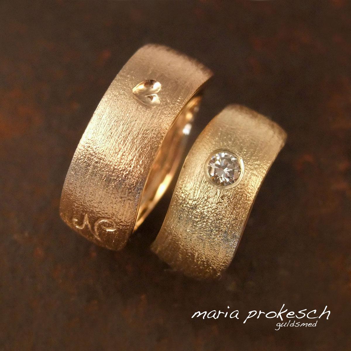 Bølgede rustikke vielsesringe i hver deres farve guld. Hendes med brillant, hans ring med et blankt hjerte som fordybning, personligt symbol