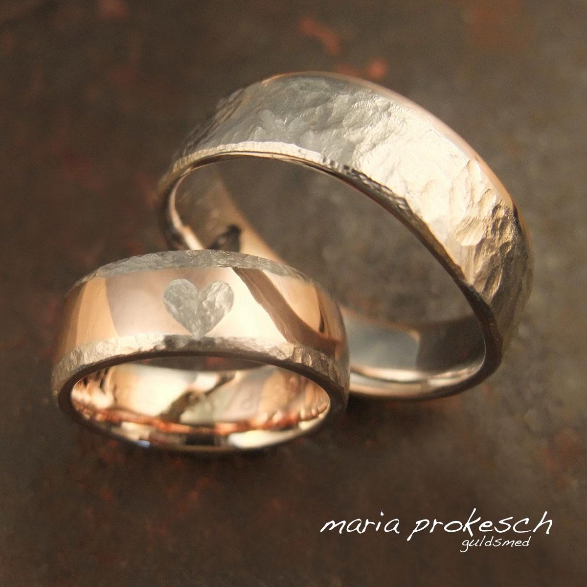 Tofarvede vielsesringe med både blank og rustik overflade. I hendes ring rustikt hvidguldshjerte omkranset af blank rosaguld.