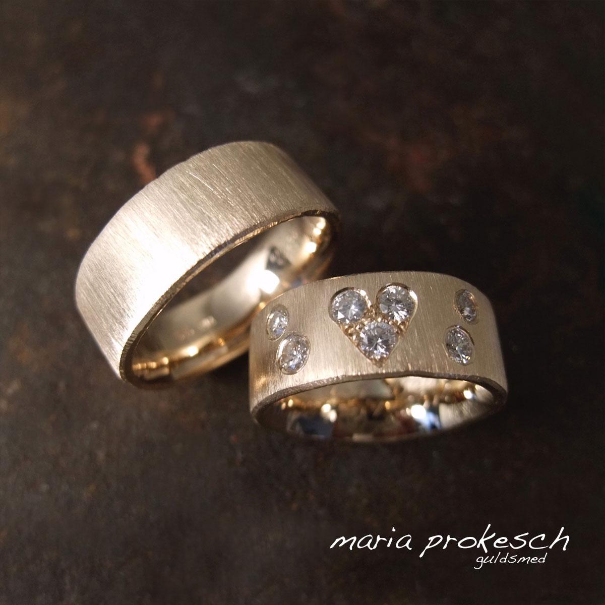 Vielsesringe i guld. Rustik rå overflade med diamanter i et hjerte til kvinden. Personlige og håndlavede af guldsmed Maria Prokesch