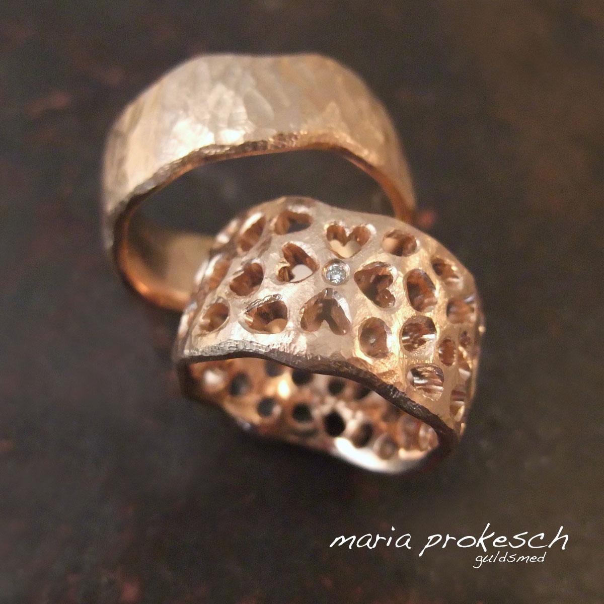 Vielsesringe i 14 kt rosaguld med udsavede hjerter, tilfældige huller og en diamant. Begge guldringe er rustikke og med buede sider.