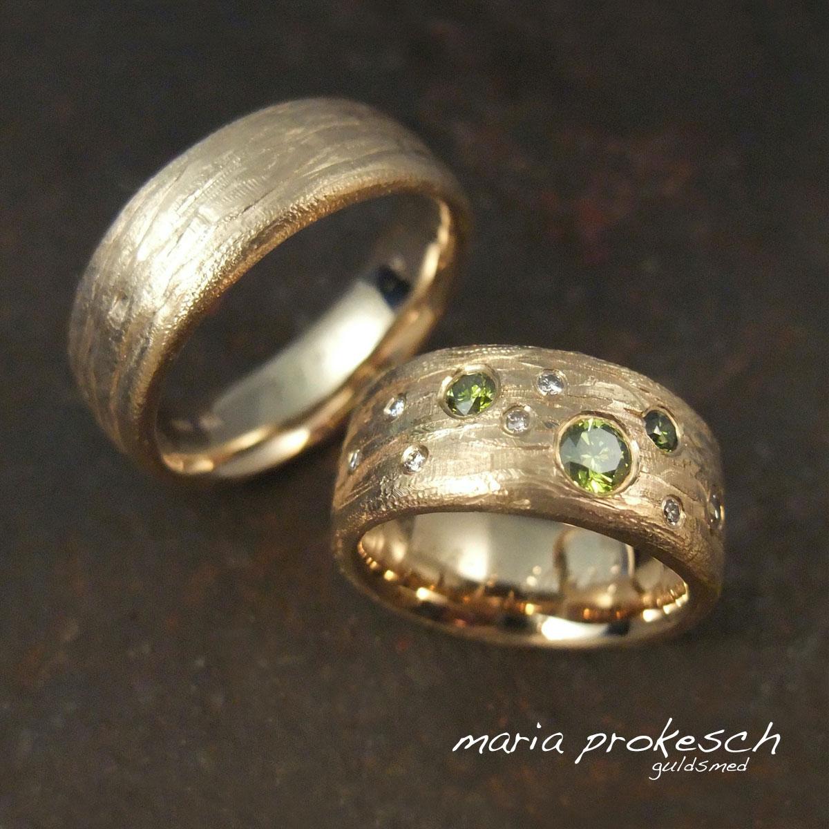 Rustikke vielsesringe i 14 kt guld med naturlig barkoverflade. På hendes ring både hvide og behandlede grønne brillanter som stjernedrys.