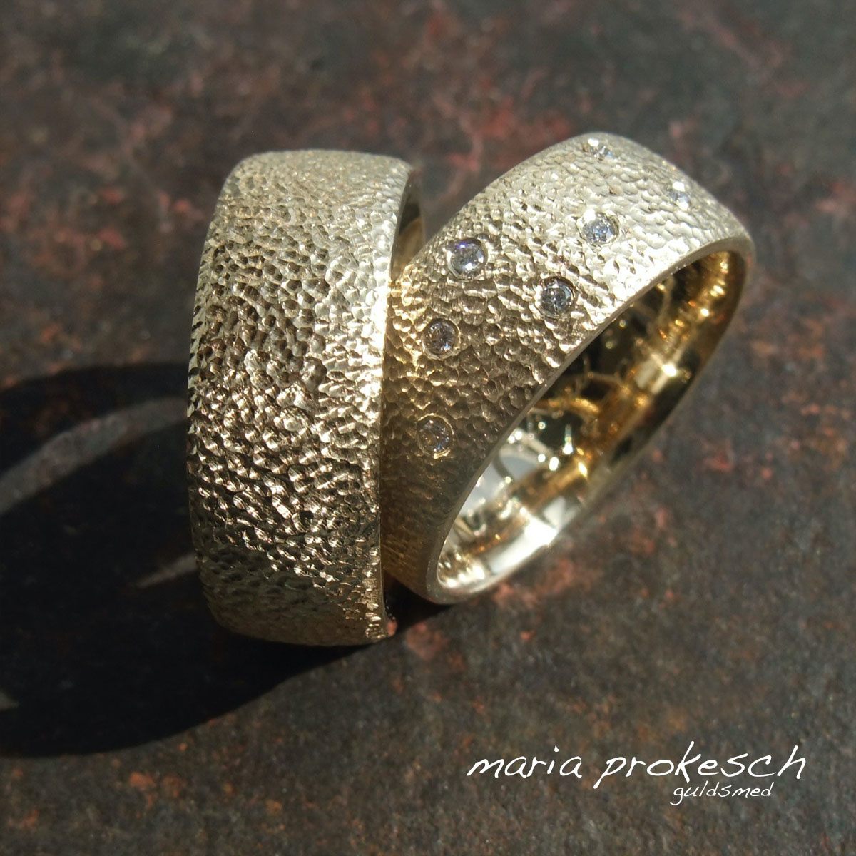 Rustikke vielsesringe i 14 kt guld med små grove fordybninger der ligner kugle hammerslået. I hendes ring små brillanter som stjernedrys