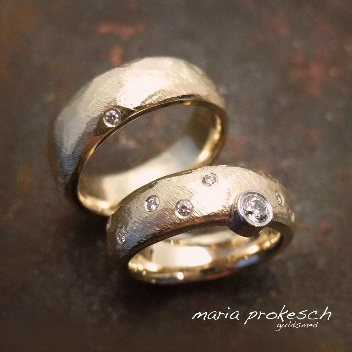 Rustikke vielsesringe i 14 kt rødguld med assymmetrisk placering af hendes store diamant. Groft filet overflade. Små brillanter pryder begge deres ringe.