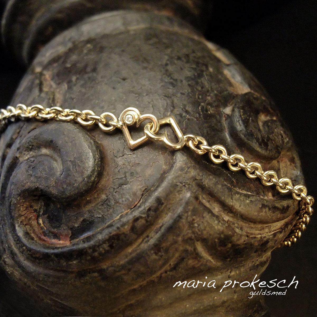 Kraftig guldarmbånd med rund ankerkæde og dobbelte hjerter der er bevægelige. I det ene hjerte sidder der på hver side en diamant.