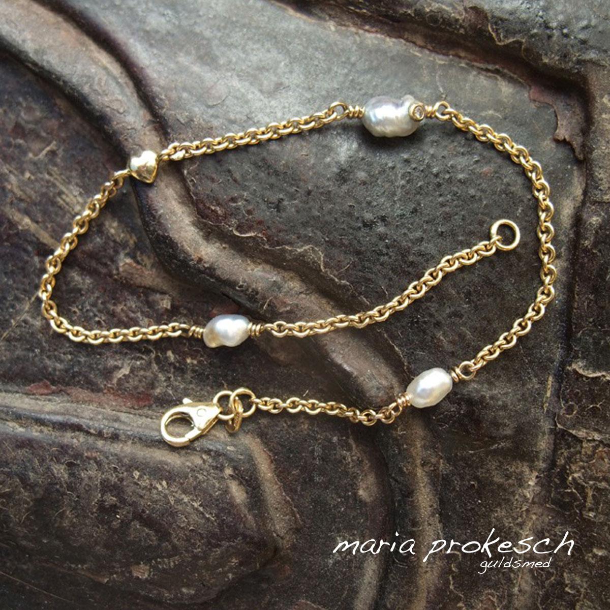 Armbånd i 14 kt guld, helt enkelt med hvide keshi perler fra South See, et lille hjerte og en diamant i den ene perle.