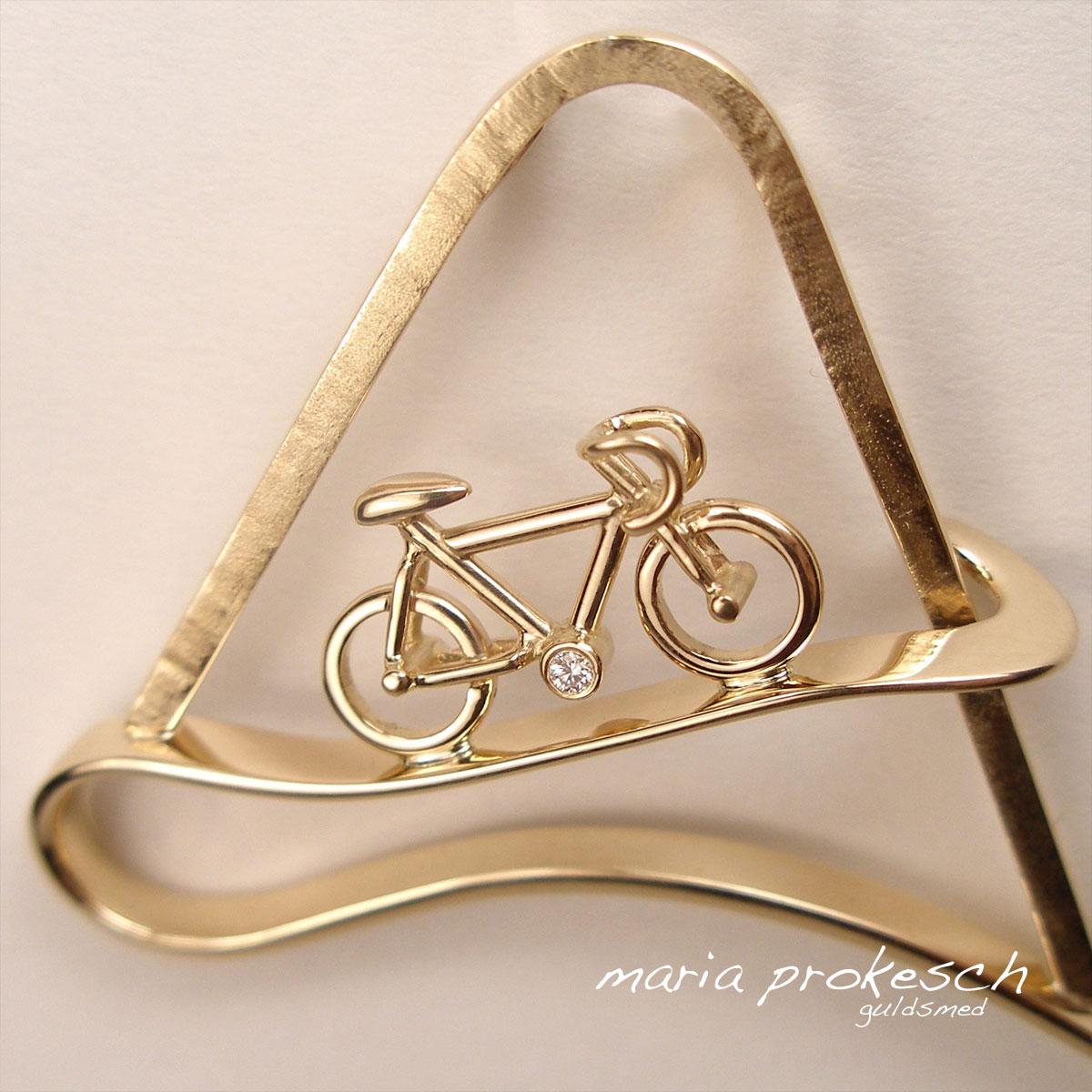 Cykel vedhæng i 14 kt guld. 11 mm høj cykel kører op ad bjergvej. Unikt smykke for cykelsport. Alt håndlavet.