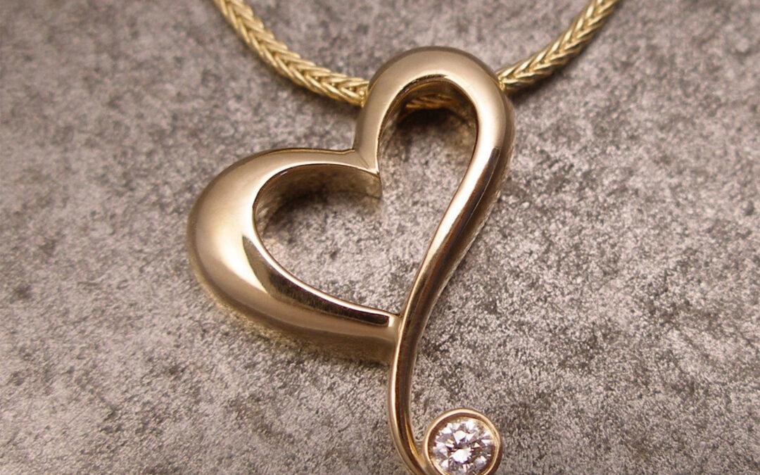 Skævt hjertevedhæng i 18 kt guld med diamant