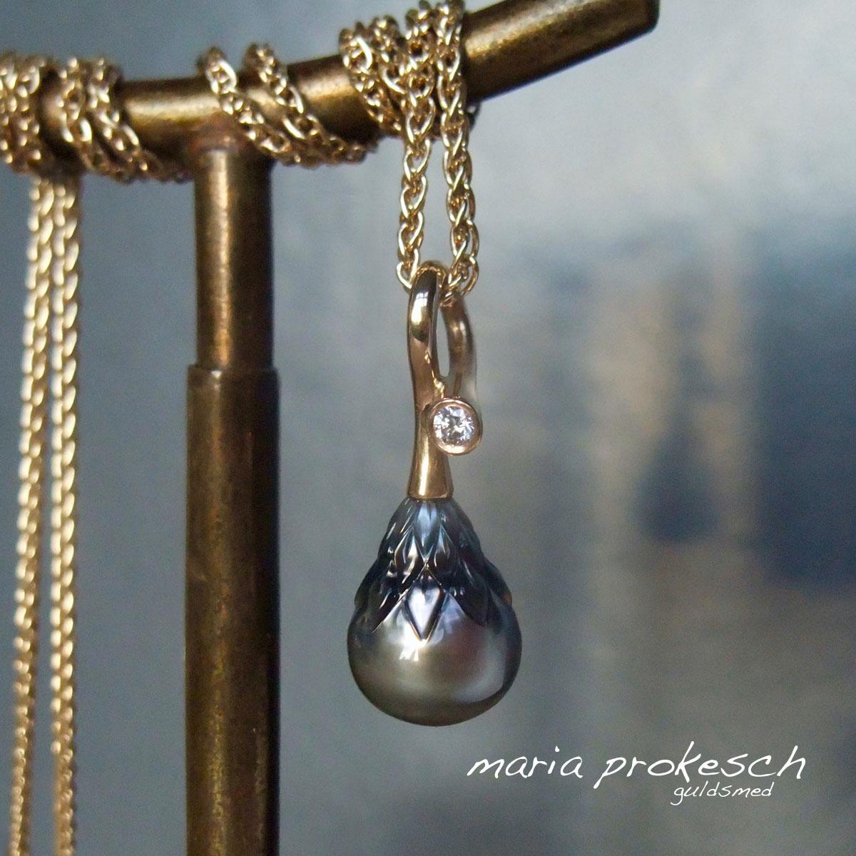 Perlevedhæng i 18 kt guld med grå Tahitiperle, facetteret med mønster i toppen. Enkelt design med diamant