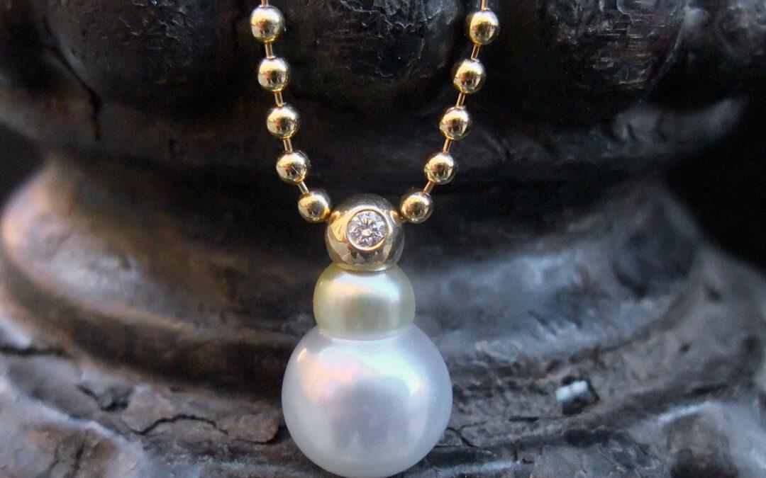 Én unika perle i to farver én guldkugle med brillant