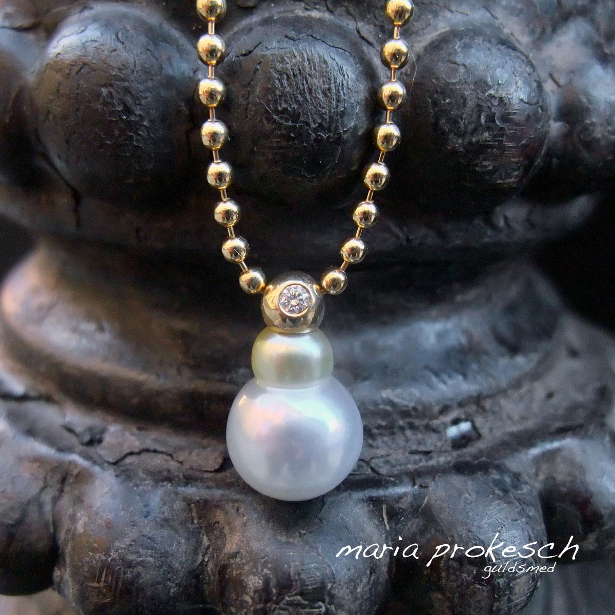 Perlevedhæng med unik South Sea perle. Muslingen har lavet en perle med to kugler der både er hvid og gul. Øverst en guldkugle i 18 kt med brillant. Kuglekæde i 14 kt guld.