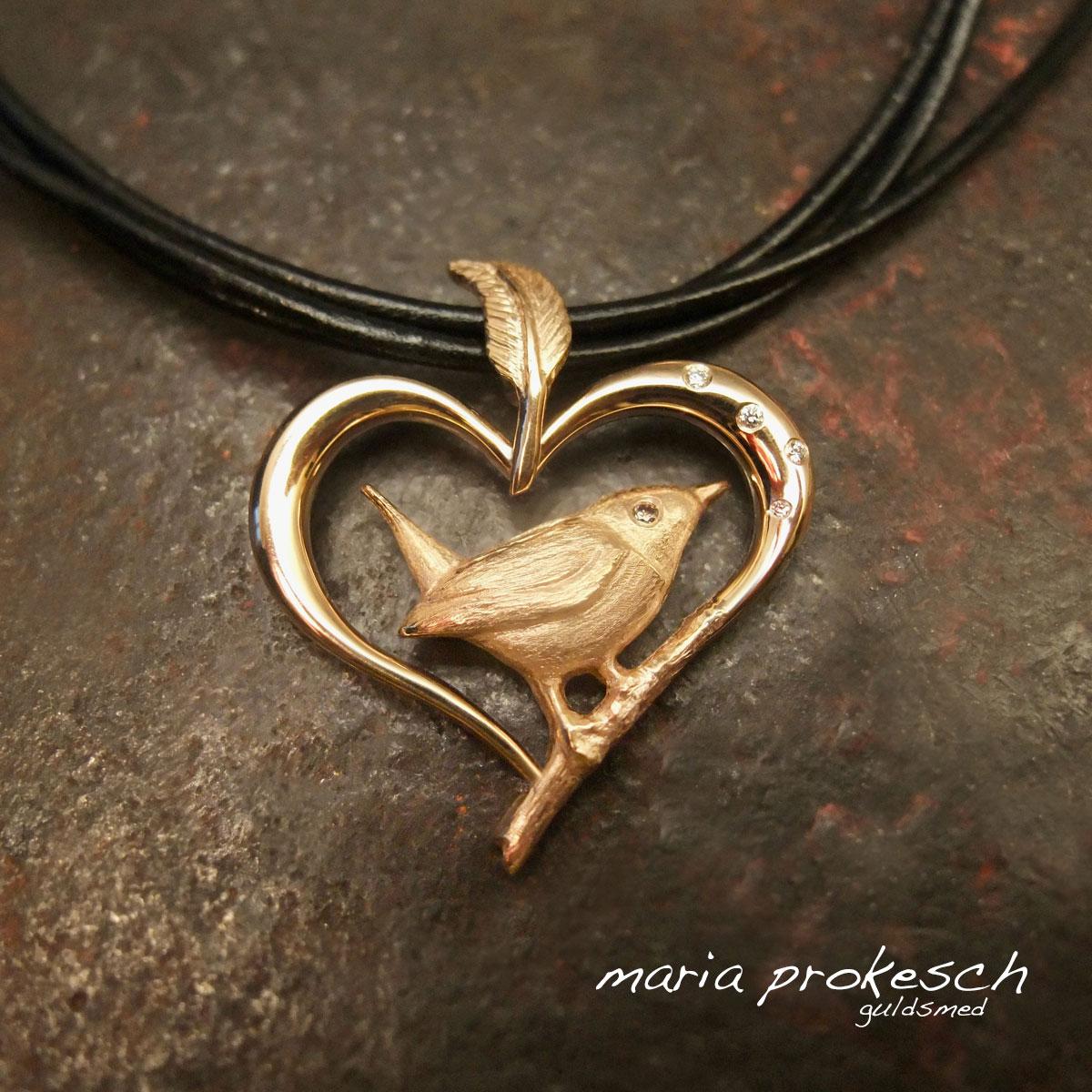 Specielt unika vedhæng med gærdesmutte. Fuglen sidder på en gren der bliver til et hjerte. Fjer som ophæng til kæde eller lædersnørre