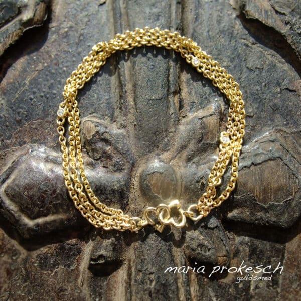 Armbånd med tre guldkæder og håndlavet hjertelås. I kæderne sidder der små fatninger med diamanter