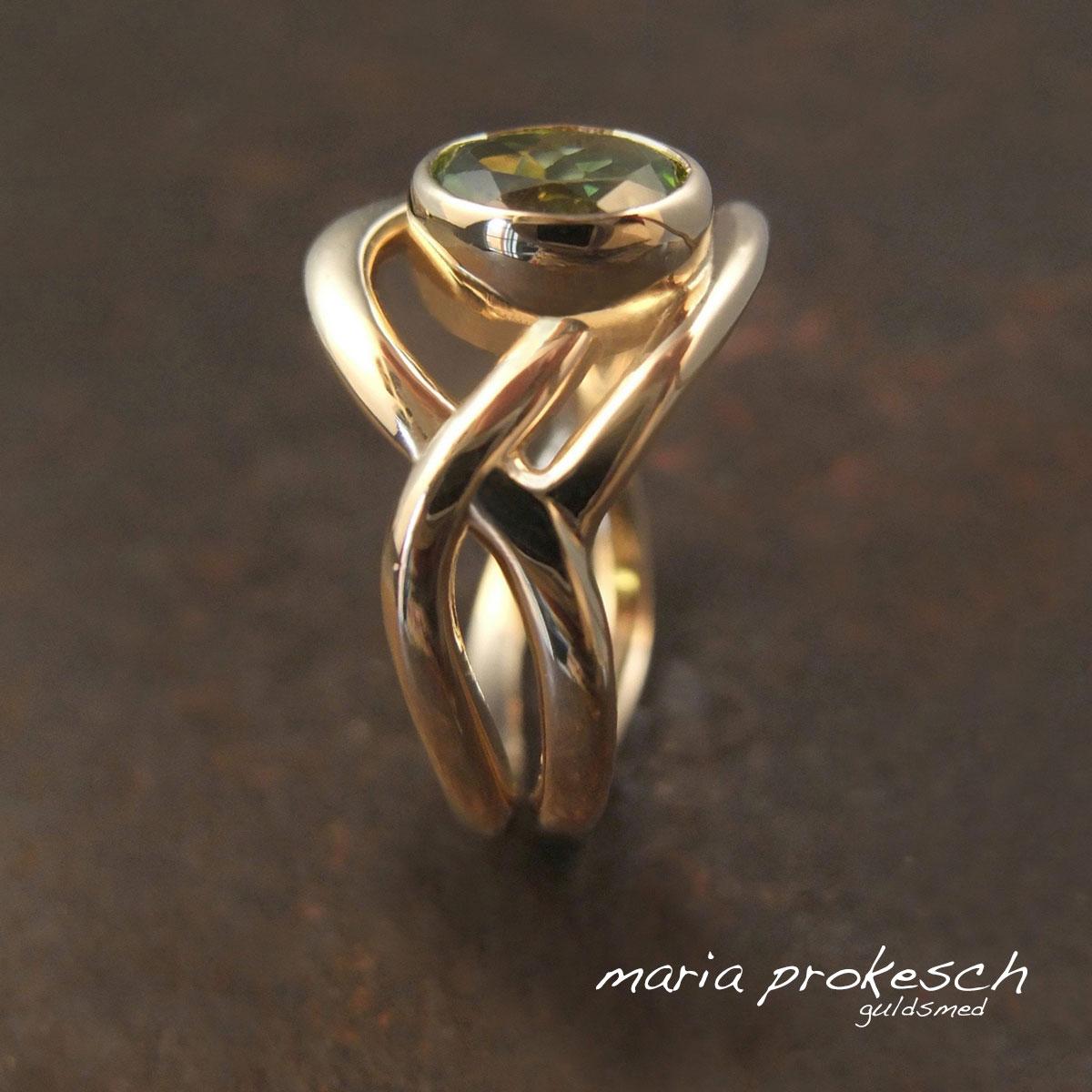 Damering i guld med blanke guldtråde som asymmetrisk buer rundt omkring grøn peridot