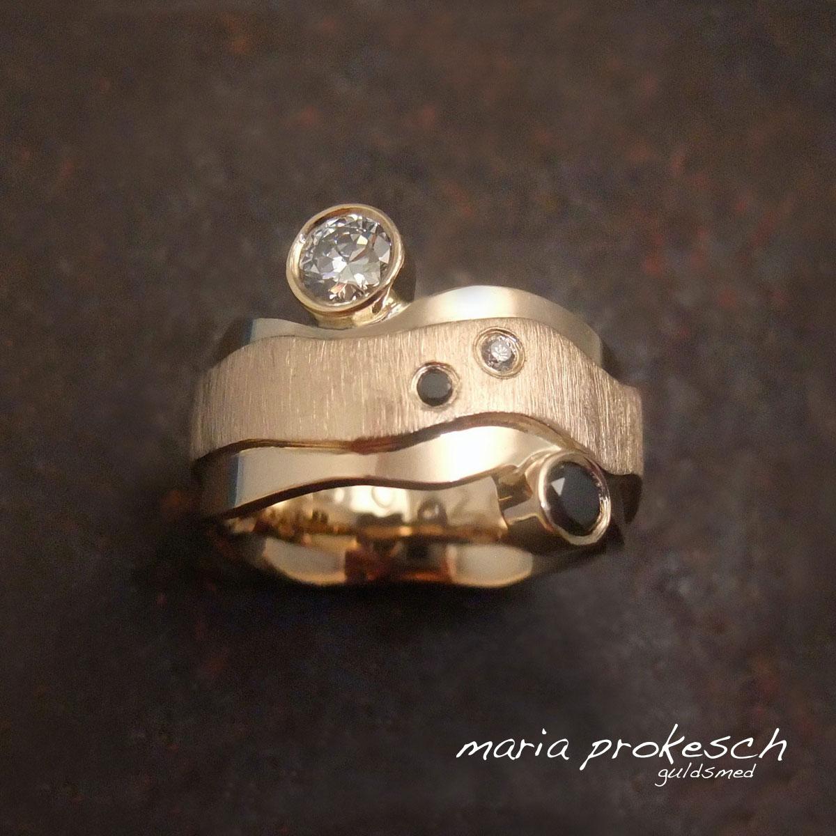 Fingerring til dame i guld med utraditionel design. Med både hvide og sorte diamanter. Håndlavet