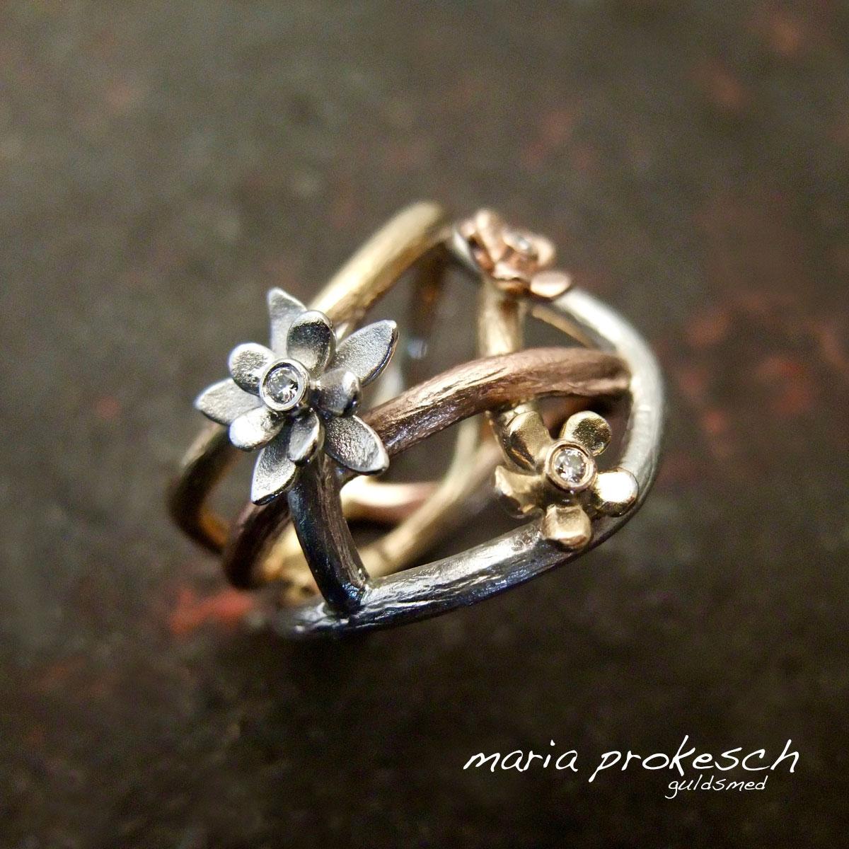 Guldring, design med tråde der flette sig smuk med tre farver guld og blomster.