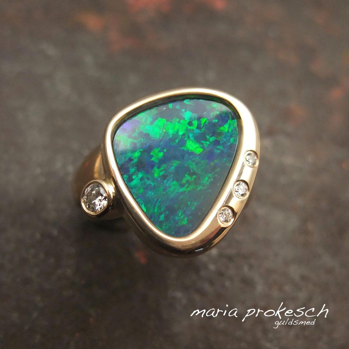 Opalring i guld med asymmetrisk design. Opalen har smukke blå og grønne farver. Diamanter som pynt