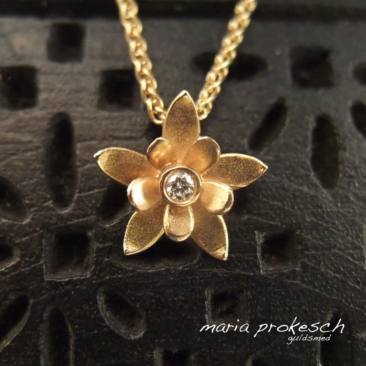 Vedhæng i 18 kt guld, blomst med dobbelte blade og diamant i midten. Lækkert design