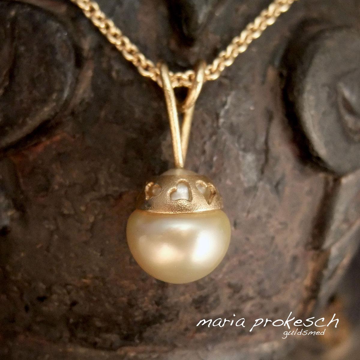 Guldvedhæng med hvid barok perle fra South Sea. Udsavede hjerter som et bånd og et anderledes hjertedesign som ophæng.