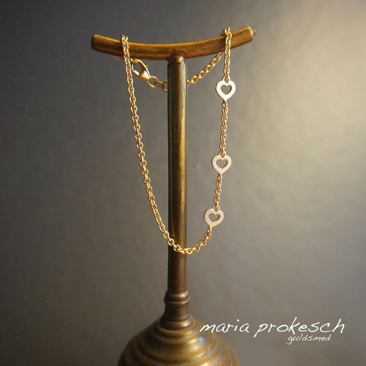 Armbånd med guldkæde og små hjerter i enkelt design som armlænke til hende