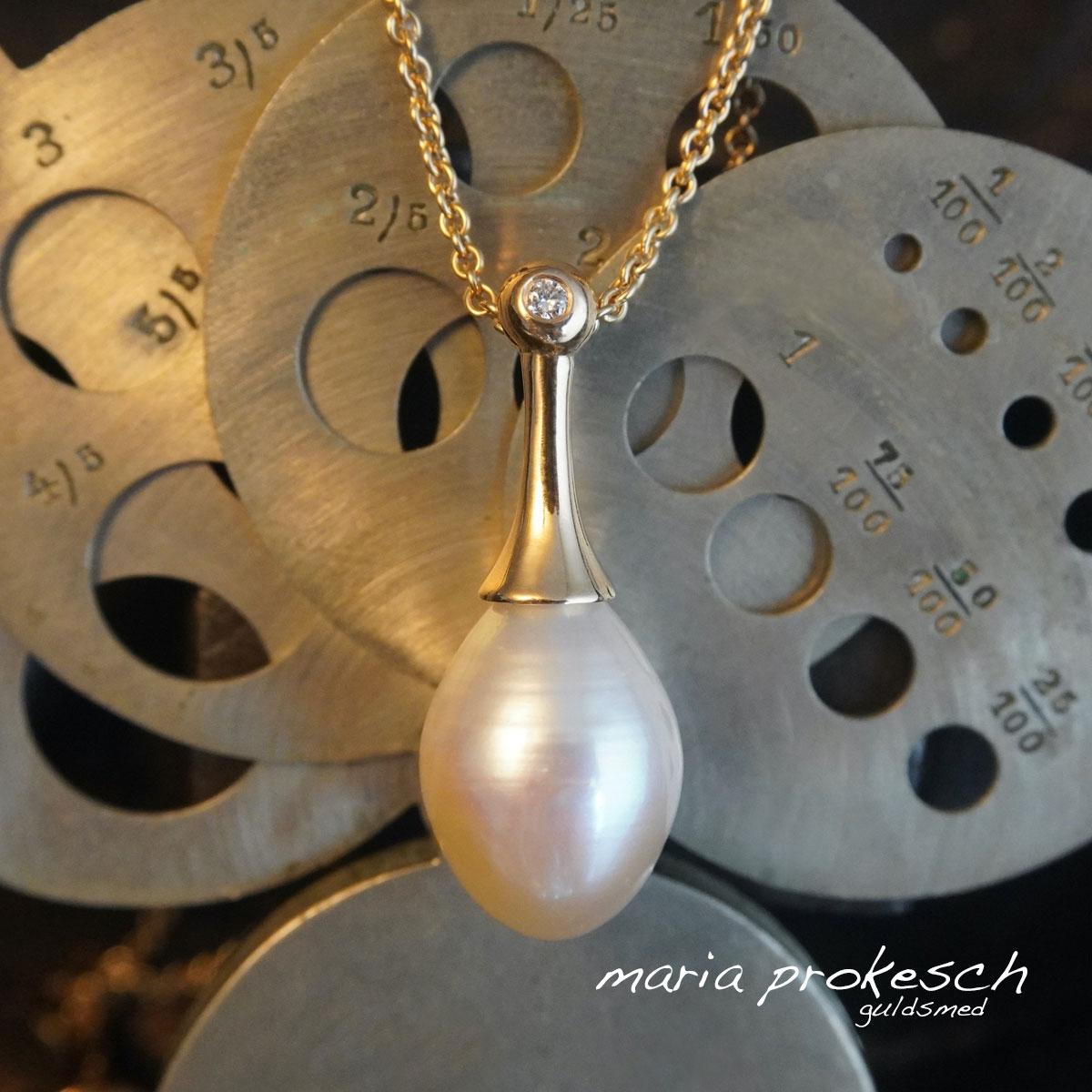 Perlevedhæng med hvid perle i 18 kt guld. Enkelt og utraditionelt design som pendul med sten, en lille diamant i toppen.
