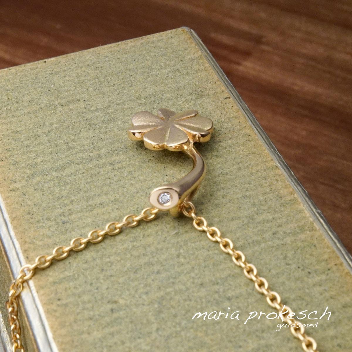 Vedhæng med firkløver i guld. For enden af stilken en diamant som ses når smykket bæres