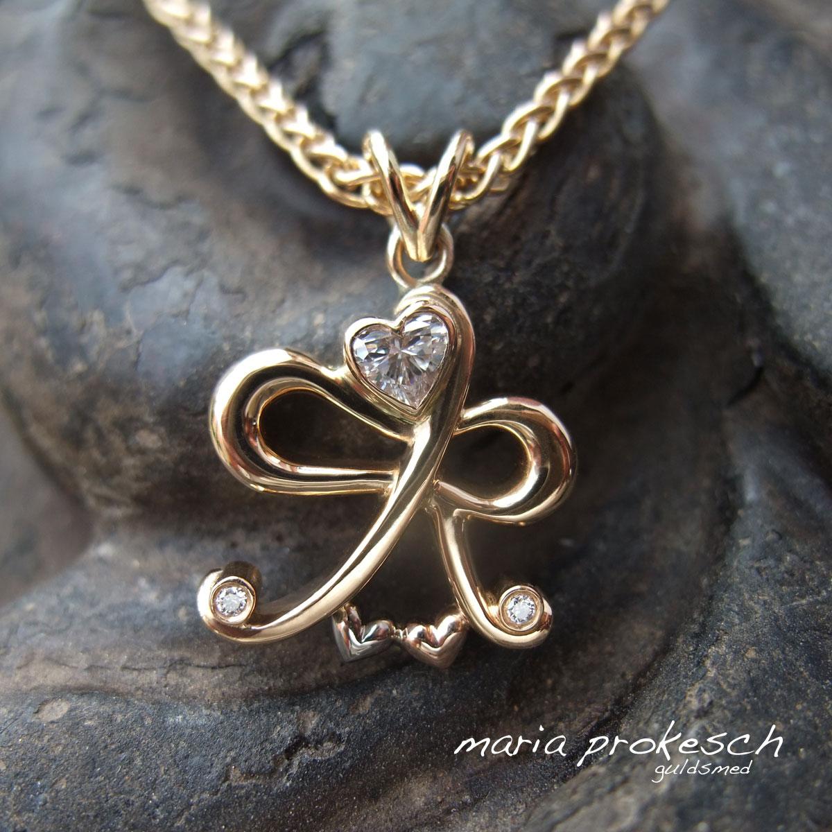 Personligt monogram som vedhæng i guld. Unika smykke med detaljer, bogstaver og hjerter. Hjerteslebet diamant og brillanter som pynt
