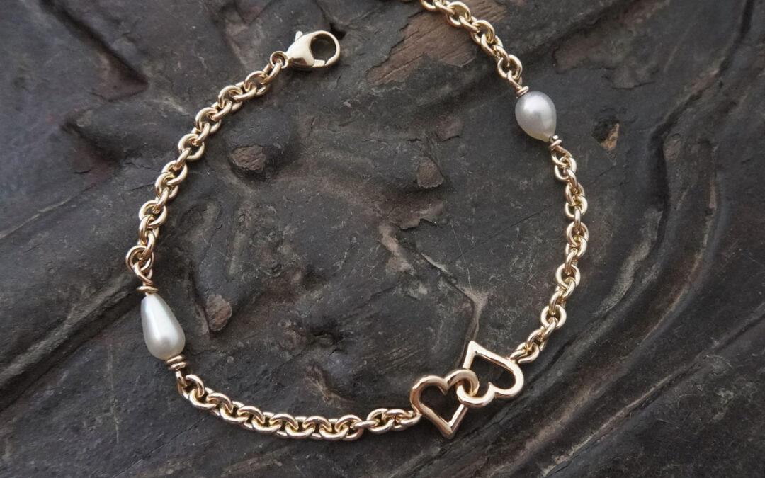 Armlænke i guld med hjerter og hvide perler