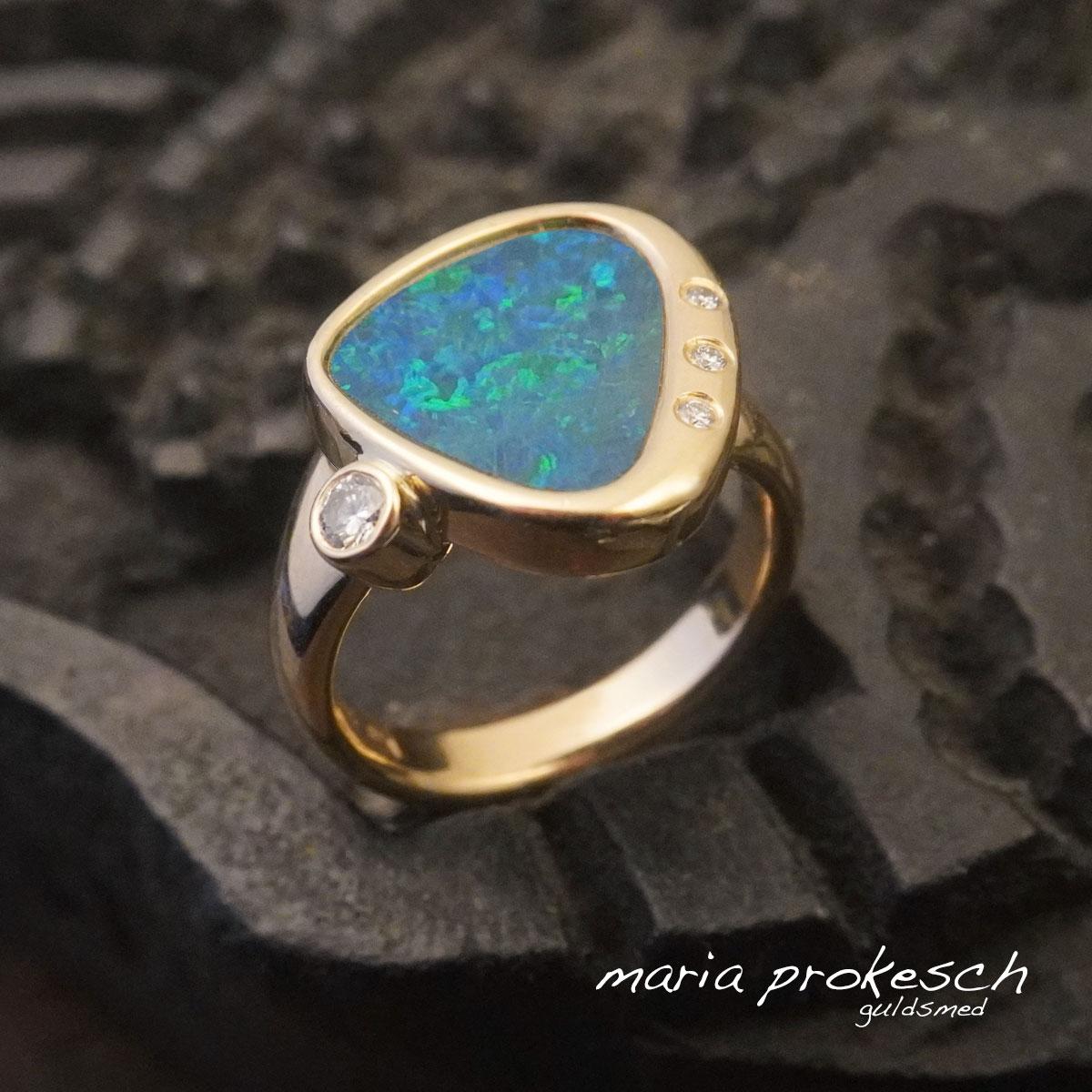 Damering med opal i blå og grønne farver. Ring  håndlavet i 14 kt guld med asymmetrisk placering af diamanter.