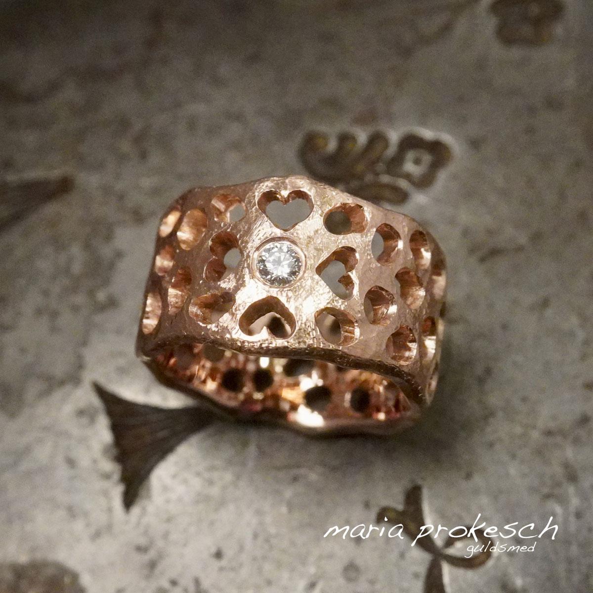 Damering i 14 kt rosaguld med udsavninger som hulmønster. Fire hjerter som symbol for familien. Rustikt håndlavet design.