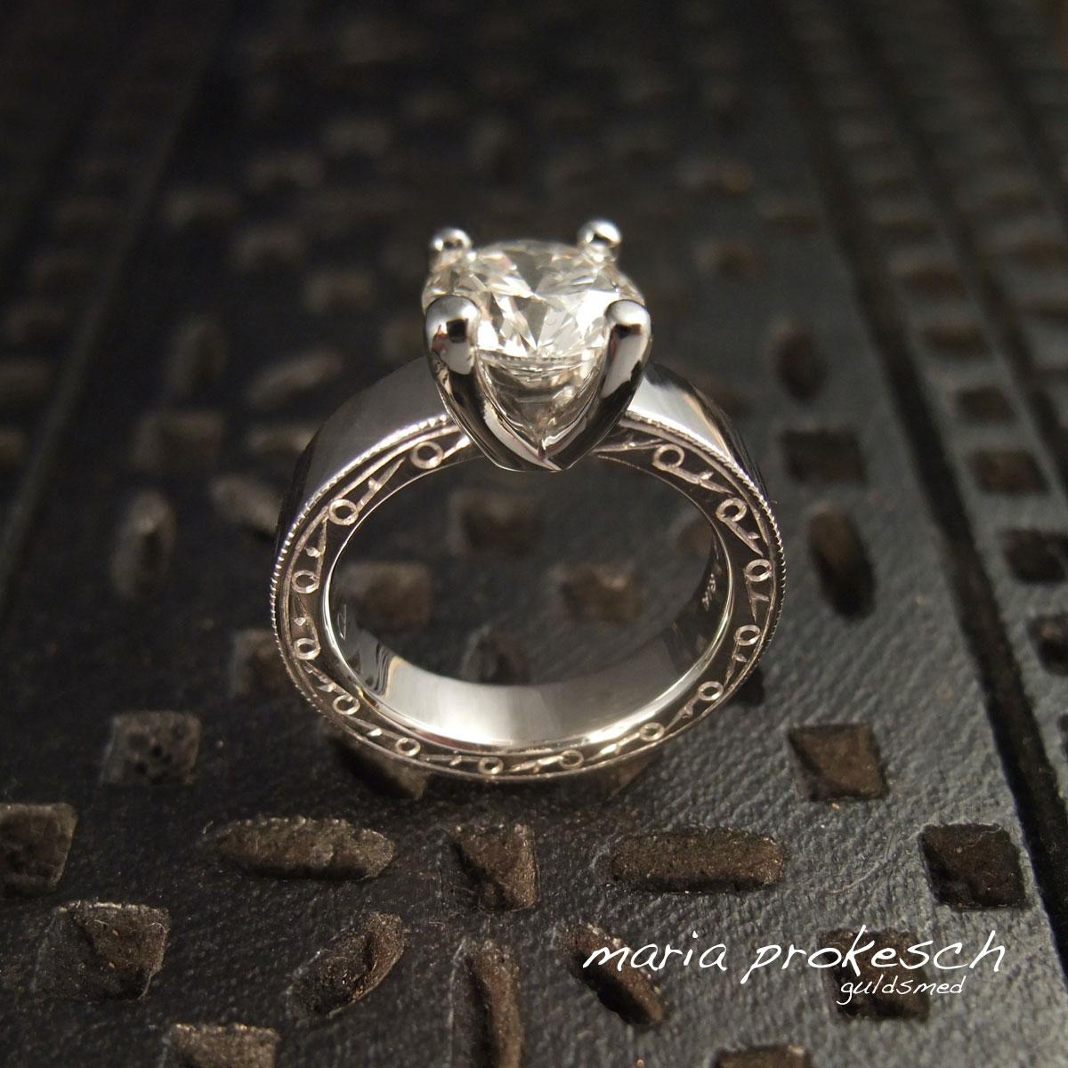 Eksklusiv hvidguldsring, solitairering. med en stor brillant i grabbefatning. Repercé graveringer på siden af ringen.